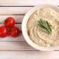 Bowl of tasty fresh hummus with tomatoes