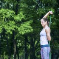 Beautiful young woman doing exercise in nature